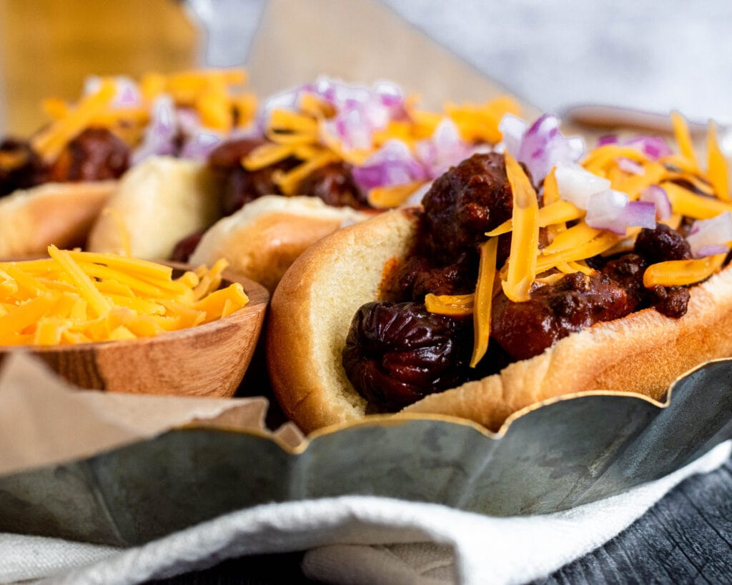 a close up eye level shot of a chili dog topped with shredded cheddar and minced red onions