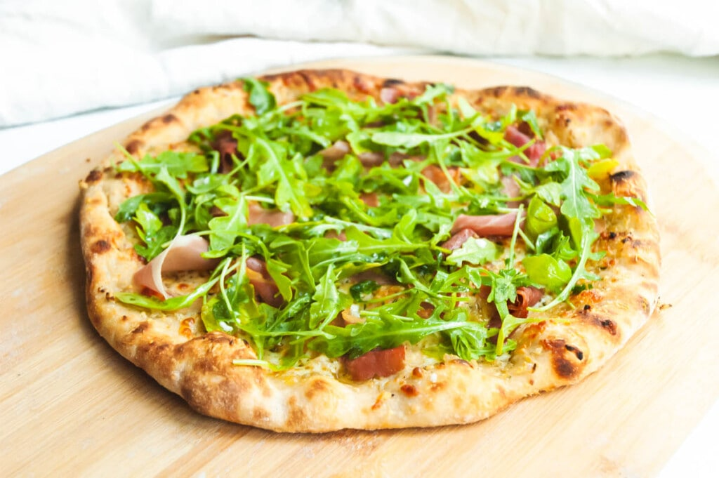 a thin bubbly crust pizza topped with fresh arugula and prosciutto sits on a wooden pizza peel