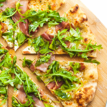 an overhead shot of a prosciutto and arugula pizza cut into 8 slices on top of a wooden pizza peel