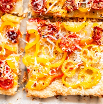 an overhead close up shot of a quarter slice of tomato and pepper tart dusted with parmesan cheese