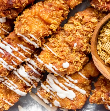 chicken tenders layered in rows on a diagonal next to each other. a zigzag of sauce has been drizzled over the left half. on the right is a small bowl of corn chex cereal.