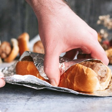 two hands wrapping a sage sausage in a hot dog bun in a sheet of aluminum foil