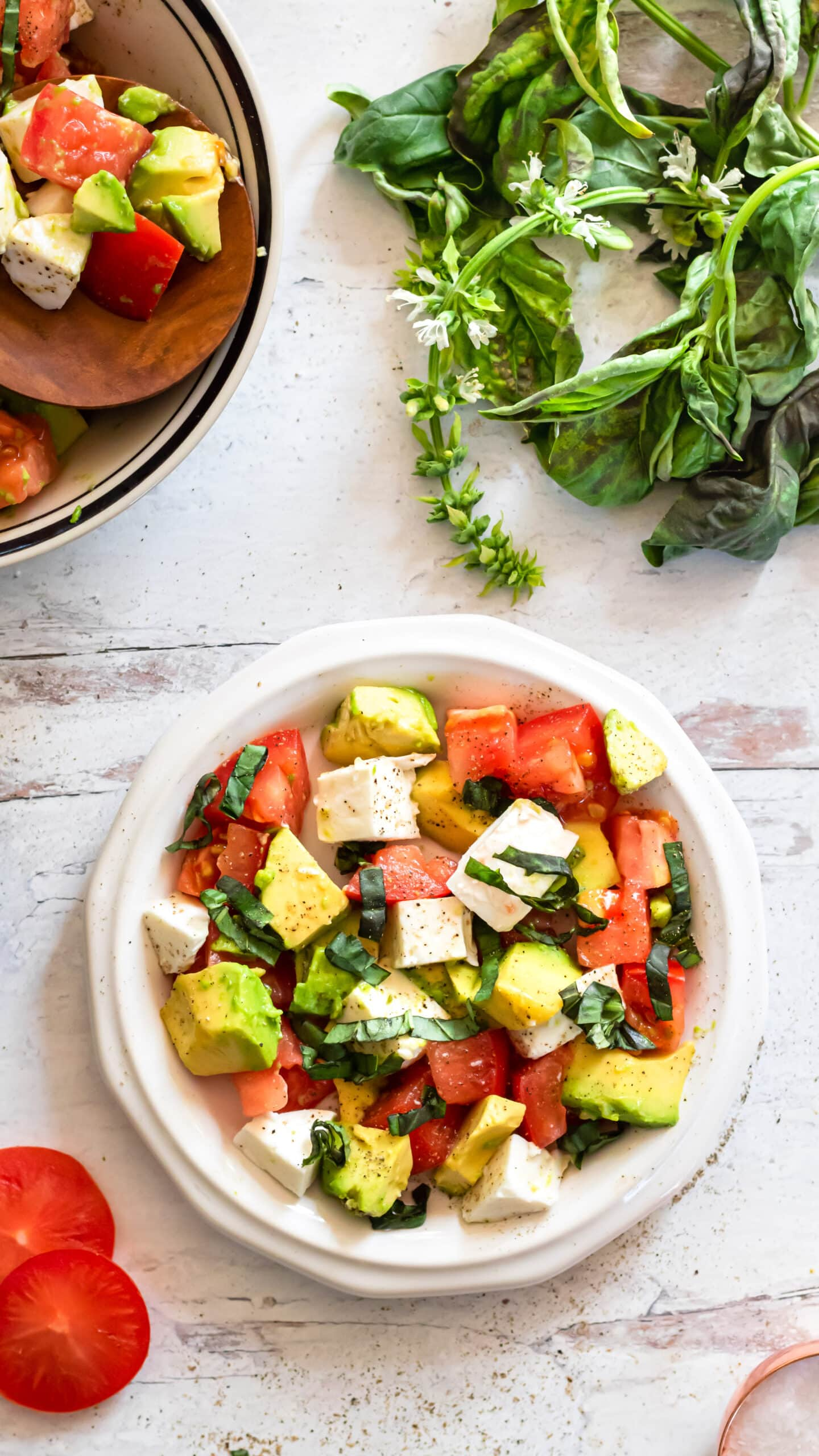a long vertical overhead photo showing a white plate of caprese salad in the bottom center. at the top of the photo slightly cropped out on the left is a bowl of salad, and on the right is a bunch of fresh basil.