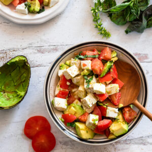 an overhead shot of a chopped caprese salad in a bowl with a wooden spoon sticking out of it. on the wooden table next to it are two tomato slices, an empty avocado skin, and some fresh basil leaves.