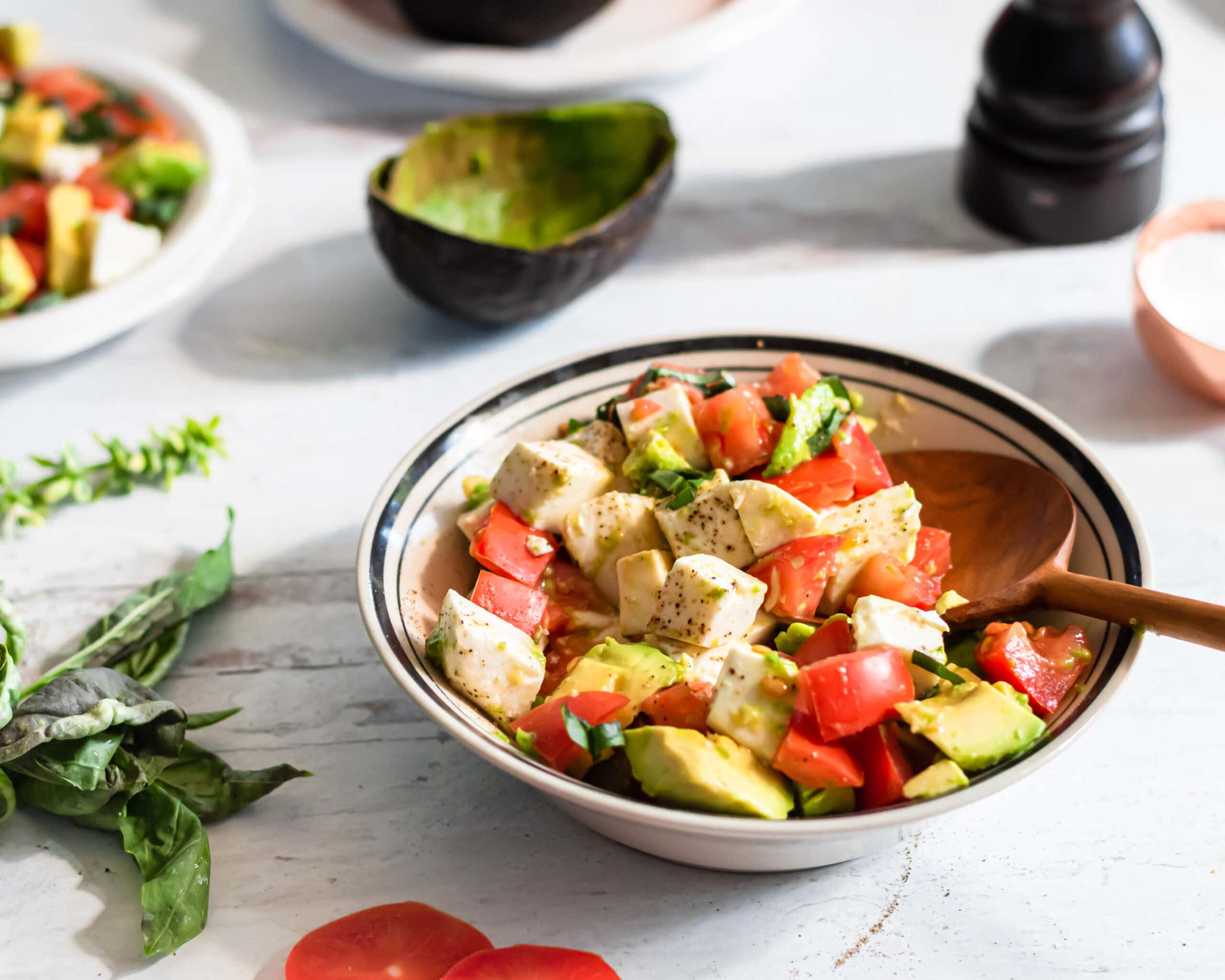 a bowl of caprese salad sits on a distressed white wooden table. an empty avocado skin is on the table behind it along with a pepper grinder, a cup of salt, and a bunch of fresh basil sits to the left of it. another plate of salad is barely cropped out in the background.