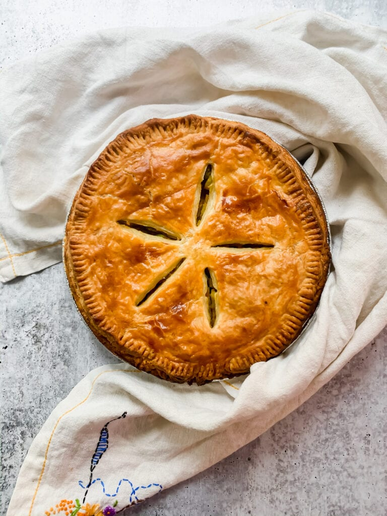 an overhead shot of a deeply golden brown pot pie with flaky puff pastry on top. five slits have been cut into the puff pastry in the shape of a star. a white dish towel is curved around the pie dish.