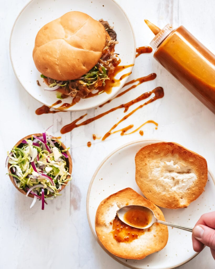 an overhead shot of two plates on a white wooden counter. the top plate has a pulled pork sandwich and a zig zag of bbq sauce across it. the bottom plate has a split open bun with a hand is using a spoon to spread half the bun with bbq sauce. a bottle of bbq sauce lies on the counter next to the plates as does a small bowl of cole slaw.