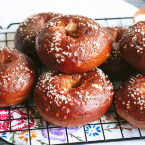 a close up of a pile of pretzel bagels on a black metal cooling rack sitting on top of an embroidered napkin.