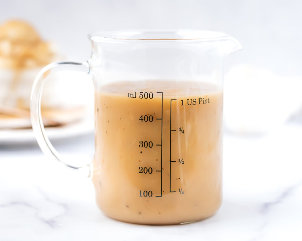 a glass measuring cup filled with 2 cups of turkey gravy. in the background you can see a ramekin with mashed potatoes and gravy poured over the top.