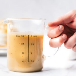 a hand holds the handle of a glass 2 cup measuring cup filled with 2 cups of turkey gravy