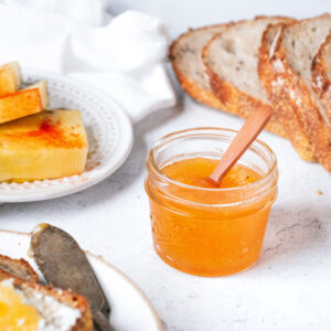 a jar of pineapple chili jam with a small wooden spoon sticking out of it. a sliced loaf of bread is behind it to the right and a plate with slices of spiced pineapple is behind it to the left.