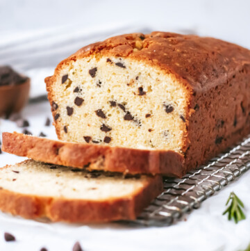 a loaf cake studded with chocolate chips sits on a small cooling rack next to some sprigs of rosemary. a small bowl of chocolate chips sits behind it.