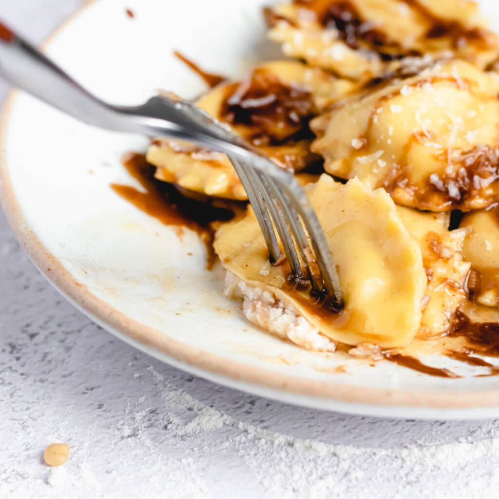 an extreme close up of a fork piercing half of a ravioli on a plate drizzled with balsamic vinegar and brown butter sauce