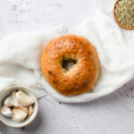 an overhead shot of a single bagel on a white linen cloth. a small bowl of garlic cloves and a small bowl of fennel seeds are in the corners of the photo.