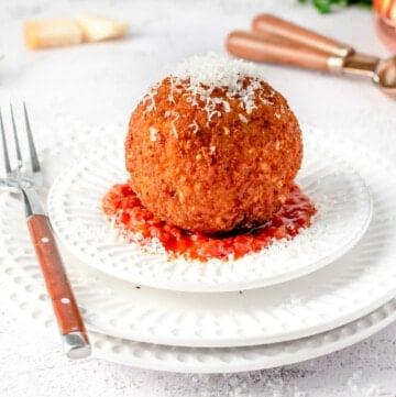 giant stuffed arancini on a plate of spaghetti sauce