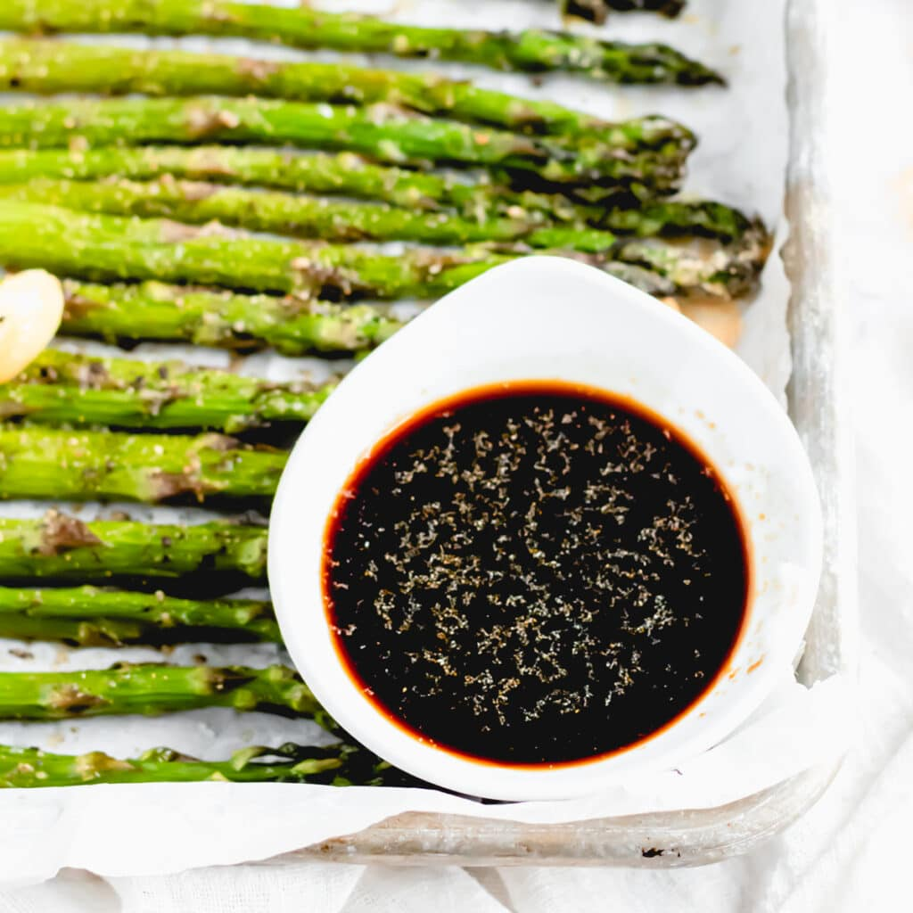 a close up of a small bowl of soy sauce with garlic powder floating on top sits on top of rows of roasted asparagus