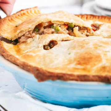 a slice of chicken pot pie being lifted out of the pie dish