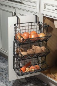 a three tier set of black wire baskets filled with onions, potatoes, and veggies hanging on the inside of a cupboard door