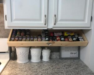 a wide shallow shelf filled with spices that can be pulled down from underneath a regular cupboard