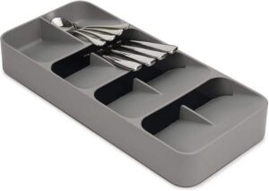 a long narrow rectangular cutlery organizer with 4 rows of 2 slots in it, each at an angle to hold utensils on top of each other in a smaller space