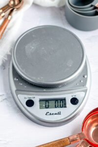 a close up of a grey round kitchen scale with nothing on it