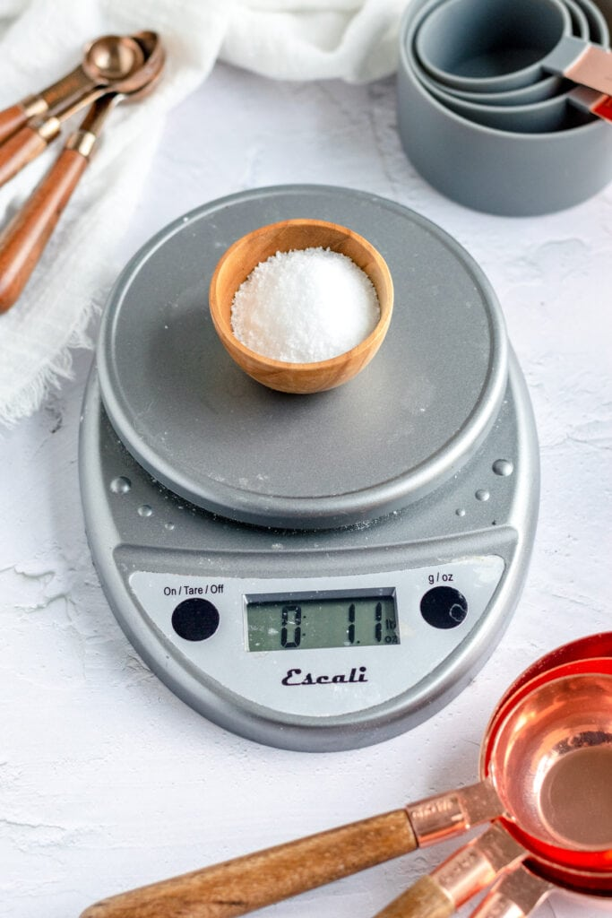 a close up of a grey round kitchen scale with a small bowl of salt on it. the display reads 1.1 oz.