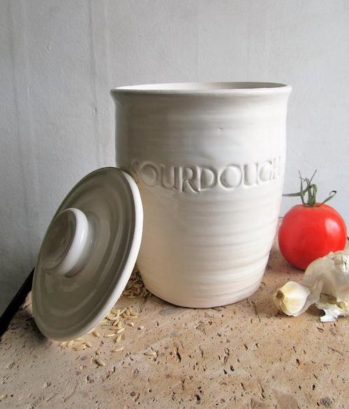 a white ceramic crock with a flat lid. the crock says SOURDOUGH.