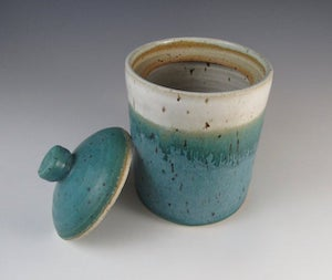 a cylindrical turquoise and white speckled sourdough container with turquoise lid