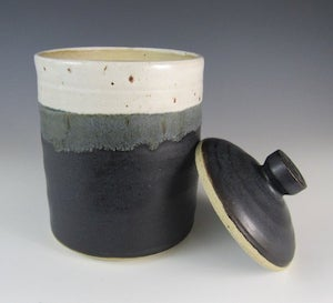 a cylindrical black, grey, and white speckled sourdough container with black lid