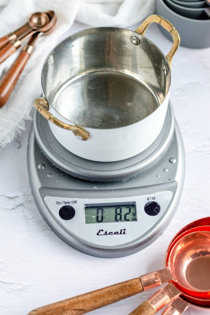 a small empty round pan with handles sits on a kitchen scale