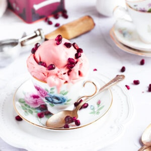 pomegranate oolong tea ice cream in a tea cup topped with pomegranate seeds