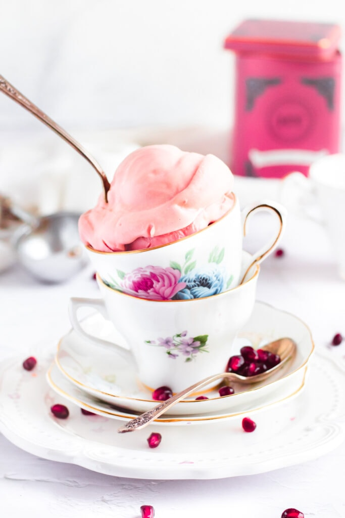 a scoop of pink ice cream in a floral tea cup with a spoon sticking out of the top