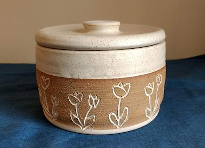 a tan and clay colored crock with a scratched tulip design around the sides