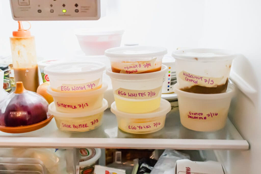 three stacks of round deli containers on the top shelf of a fridge neatly labeled with masking tape