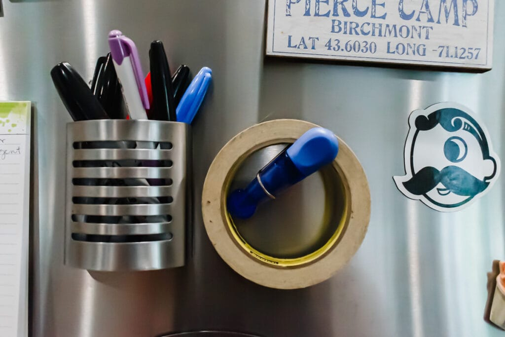 a metal cup of pens and markers on the fridge door with a roll of masking tape hanging next to it