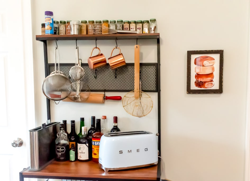 the top half of the baker's rack with toaster oven, hanging tools, and spices along the top