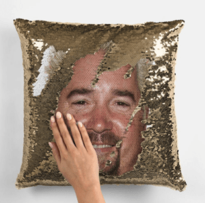 a gold sequined pillow with some of the sequins flipped up to reveal guy fieri's face