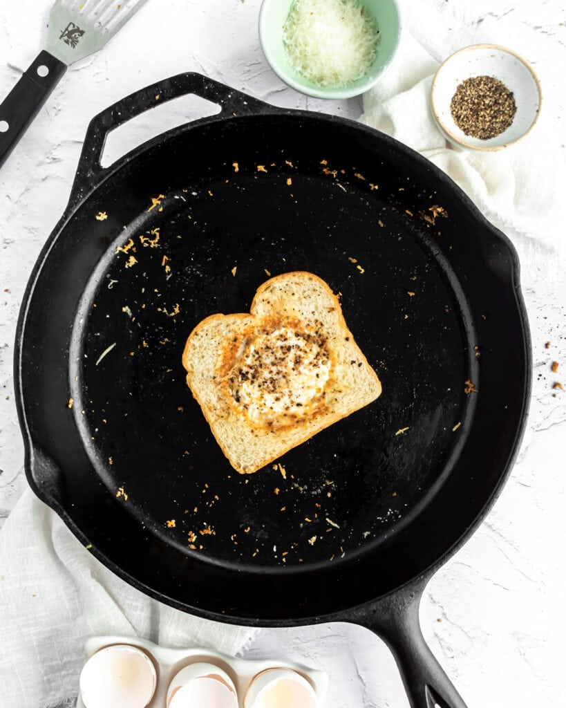 a slice of bread with an egg cooked through in the center sits in the center of a large cast iron pan