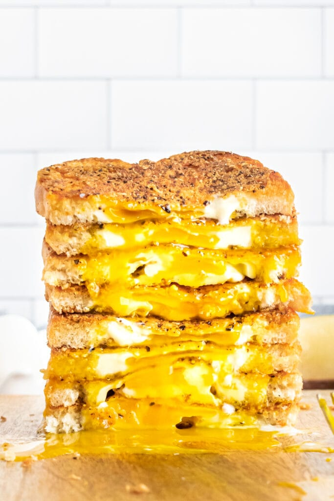 a tower of cacio e pepe egg in a basket toasts cut in half, the insides all facing forward with yolks running down onto a wooden cutting board
