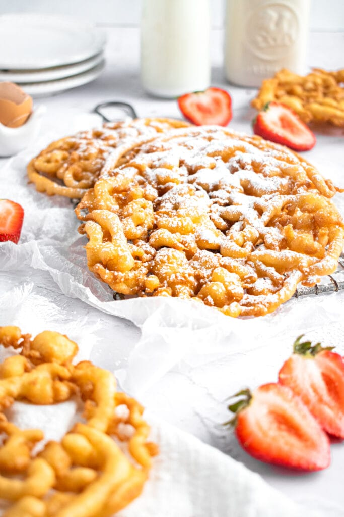 a straight on shot of funnel cakes on a white dish cloth surrounded by strawberry halves