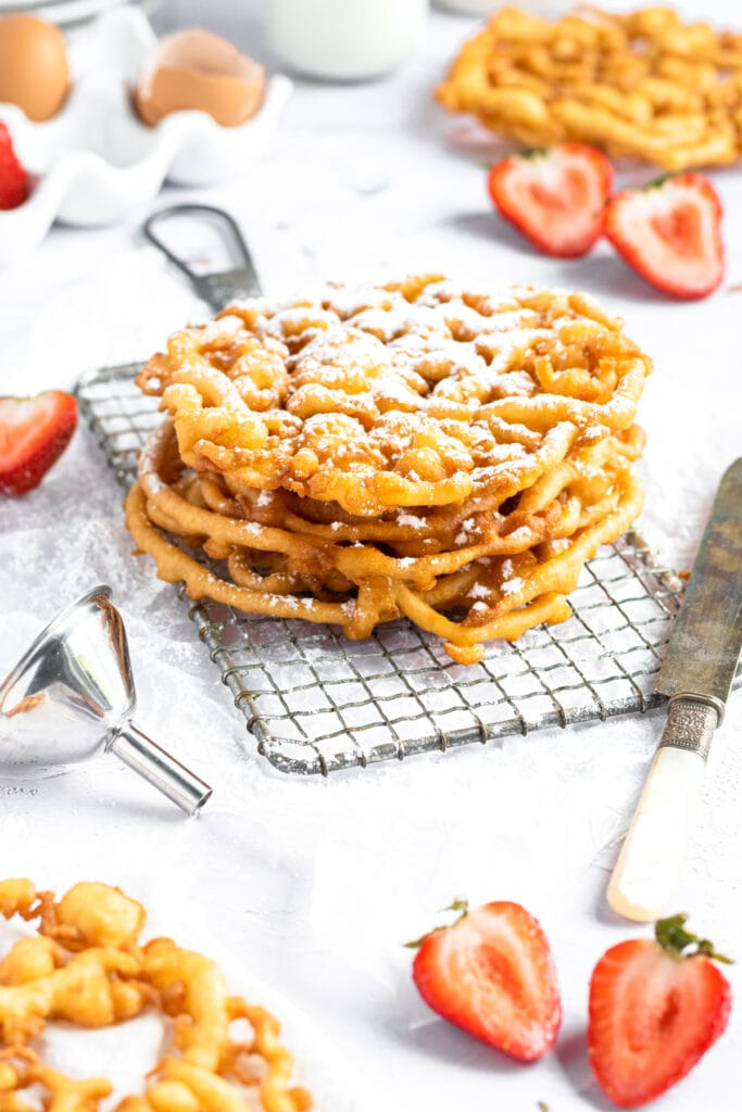 a stack of funnel cakes on a small cooling rack surrounded by strawberries and other funnel cakes