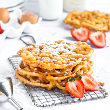 A stack of 3 funnel cakes on a small cooling rack. two halves of a strawberry sit in front of them.
