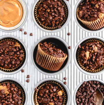 an overhead shot of a muffin tin with 8 chocolate muffins and one filled with peanut butter