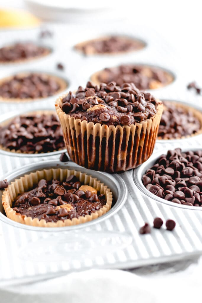 a chocolate muffin sits on top of a muffin tin with other muffins in the wells around it