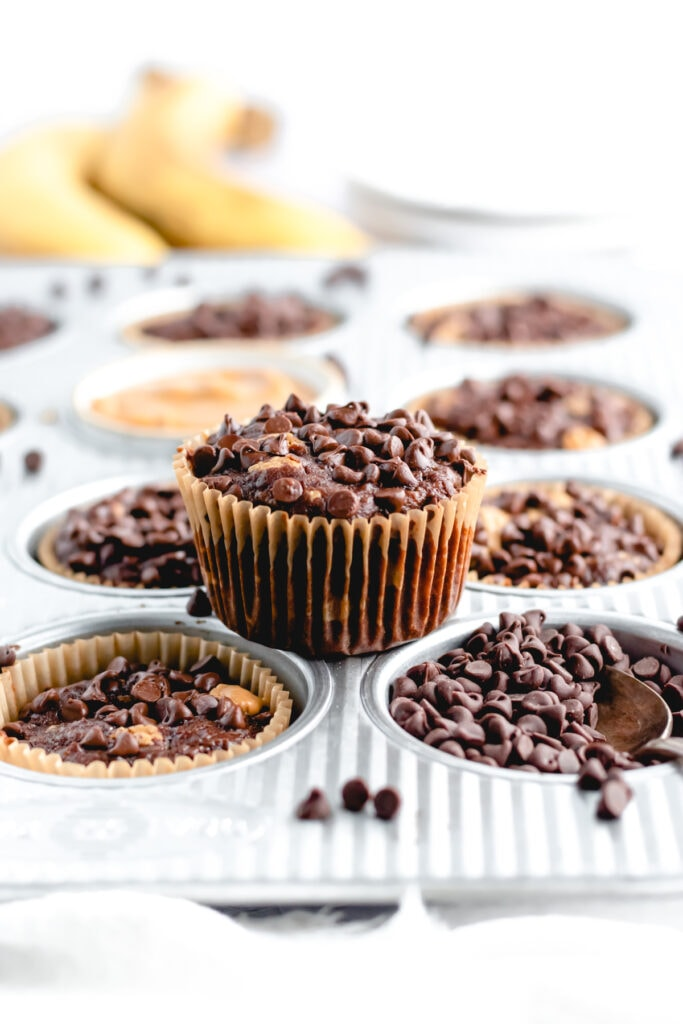 a chocolate banana muffin sits on top of a muffin tin filled with other muffins