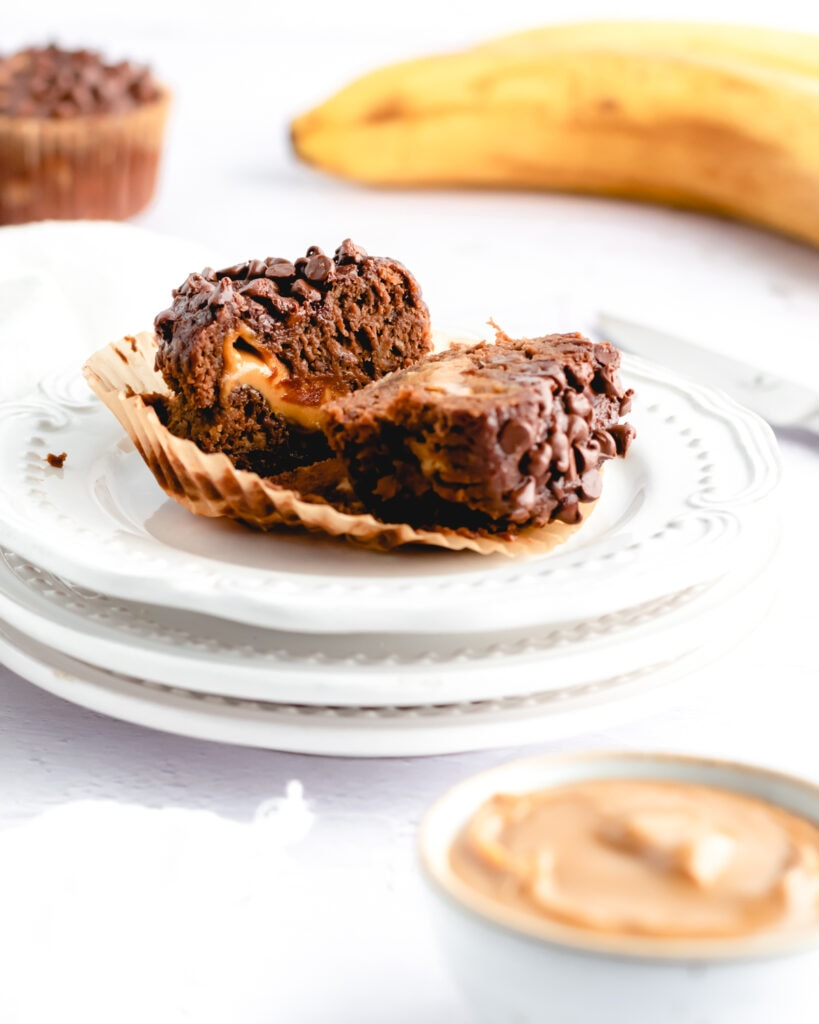 a chocolate banana muffin cut in half on a stack of small plates revealing the peanut butter center