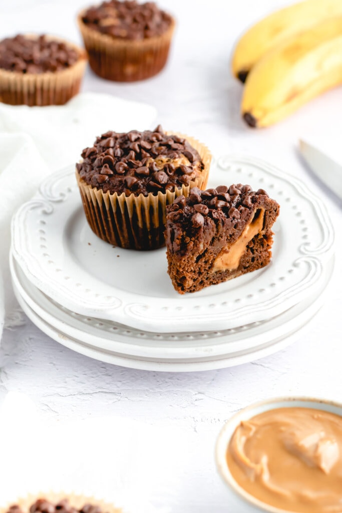 a chocolate banana muffin sits on a plate with half of a chocolate banana muffin
