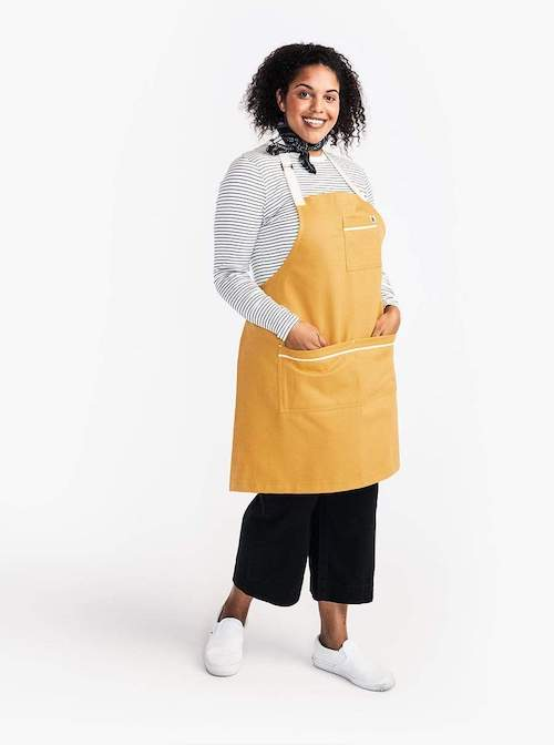 a woman wearing a yellow apron with a white strap