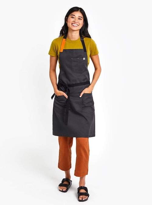 a woman wearing a navy grey apron with one orange strap and one navy strap