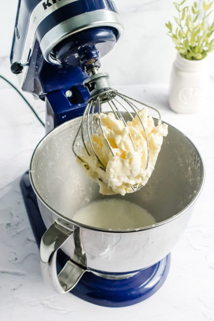 a stand mixer with the head tilted back showing butter collected inside the wire whisk and buttermilk in the mixer bowl
